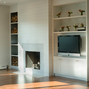 Large danish enclosed medium tone wood floor family room photo in New York with white walls, a standard fireplace, a stone fireplace and no tv
