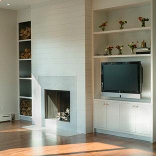 Diseño de sala de estar cerrada, escandinava, grande, sin televisor, con paredes blancas, suelo de madera en tonos medios, chimenea tradicional y marco de chimenea de piedra