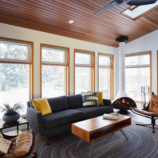 エドモントンの中サイズのミッドセンチュリースタイルのおしゃれなファミリールーム (白い壁、磁器タイルの床、吊り下げ式暖炉、グレーの床) の写真