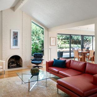 ポートランドの中サイズのミッドセンチュリースタイルのおしゃれなファミリールーム (白い壁、淡色無垢フローリング、標準型暖炉、レンガの暖炉まわり、内蔵型テレビ、茶色い床) の写真