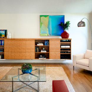 Diseño de sala de estar abierta, retro, de tamaño medio, sin chimenea, con paredes blancas, suelo de madera clara, televisor retractable y suelo marrón