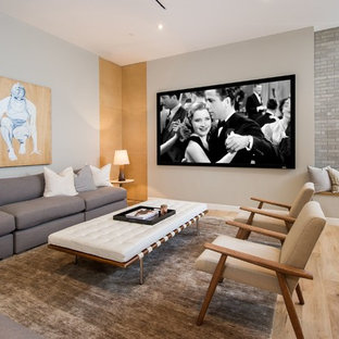 Example of a large 1960s open concept light wood floor family room design in Los Angeles with gray walls