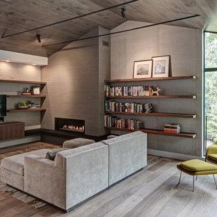 Foto de sala de estar con biblioteca abierta, vintage, con paredes grises, suelo de madera clara, chimenea lineal, marco de chimenea de baldosas y/o azulejos y televisor colgado en la pared