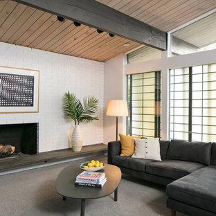 シアトルの小さいミッドセンチュリースタイルのおしゃれなオープンリビング (白い壁、カーペット敷き、標準型暖炉、レンガの暖炉まわり、コーナー型テレビ、グレーの床) の写真