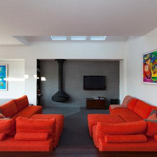 Idee per un soggiorno design aperto con pareti grigie e TV a parete