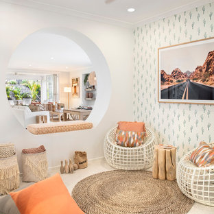 This is an example of a beach style family room in Brisbane with white walls and beige floor.