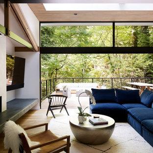 Idee per un soggiorno costiero aperto con pareti bianche, pavimento in legno massello medio, camino lineare Ribbon, cornice del camino in cemento, TV a parete e soffitto in legno