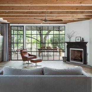 Diseño de sala de estar con barra de bar de estilo de casa de campo con paredes blancas, suelo de madera clara, chimenea de esquina y suelo beige