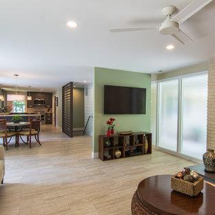 ボルチモアの中サイズのコンテンポラリースタイルのおしゃれなファミリールーム (ベージュの壁、磁器タイルの床、標準型暖炉、レンガの暖炉まわり、壁掛け型テレビ、ベージュの床) の写真