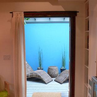 Diseño de sala de estar con biblioteca tipo loft, marinera, pequeña, con paredes blancas, suelo de bambú y pared multimedia