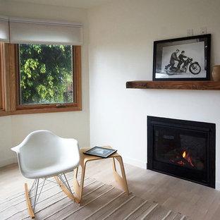 Diseño de sala de estar abierta, romántica, pequeña, sin televisor, con paredes blancas, suelo de madera clara, chimenea tradicional y marco de chimenea de yeso