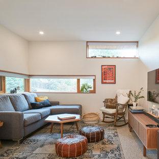 バンクーバーの中サイズのミッドセンチュリースタイルのおしゃれなファミリールーム (白い壁、コンクリートの床、グレーの床、壁掛け型テレビ) の写真