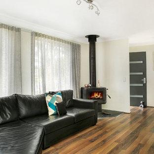 ウロンゴンの小さいカントリー風おしゃれな独立型ファミリールーム (白い壁、無垢フローリング、コーナー設置型暖炉、金属の暖炉まわり、壁掛け型テレビ、マルチカラーの床) の写真