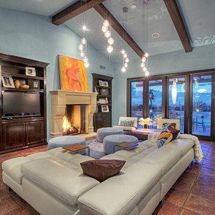 Foto di un ampio soggiorno minimalista aperto con pareti blu, pavimento in terracotta, camino classico, cornice del camino in pietra e parete attrezzata