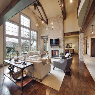 Family room - rustic dark wood floor family room idea in Dallas with beige walls, a standard fireplace, a stone fireplace and a wall-mounted tv