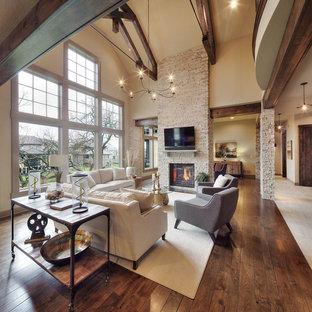 Rustikales Wohnzimmer mit beiger Wandfarbe, dunklem Holzboden, Kamin, Kaminumrandung aus Stein und Wand-TV in Dallas
