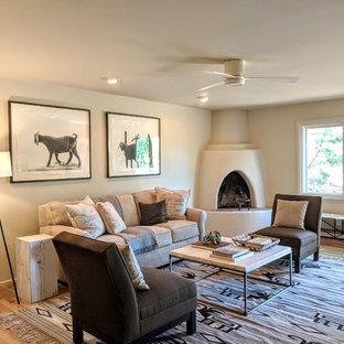 他の地域の大きいサンタフェスタイルのおしゃれな独立型ファミリールーム (白い壁、淡色無垢フローリング、コーナー設置型暖炉、漆喰の暖炉まわり、据え置き型テレビ、茶色い床) の写真