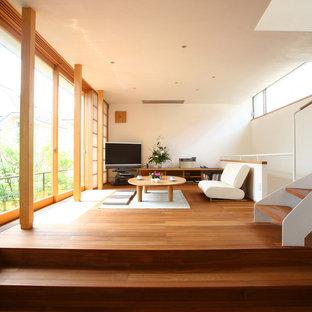 Asiatisches Wohnzimmer mit weißer Wandfarbe, braunem Holzboden und Eck-TV in San Diego