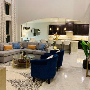オースティンの広いモダンスタイルのおしゃれなオープンリビング (ベージュの壁、大理石の床、コーナー設置型暖炉、タイルの暖炉まわり、白い床、据え置き型テレビ) の写真
