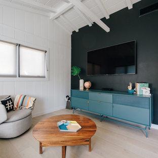 Esempio di un piccolo soggiorno stile marinaro chiuso con sala giochi, pareti nere, parquet chiaro, TV a parete e pavimento beige