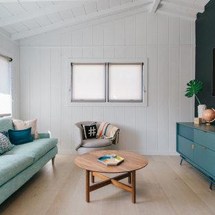 Idée de décoration pour une petite salle de séjour marine fermée avec un mur noir, un sol en bois clair, un téléviseur fixé au mur et un sol beige.