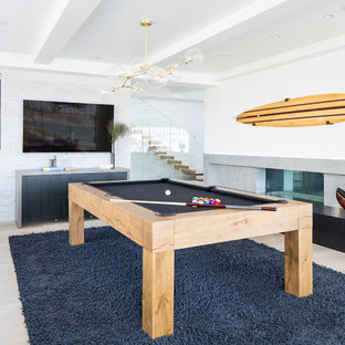Inspiration for a beach style light wood floor and beige floor game room remodel in Orange County with white walls, a ribbon fireplace and a wall-mounted tv