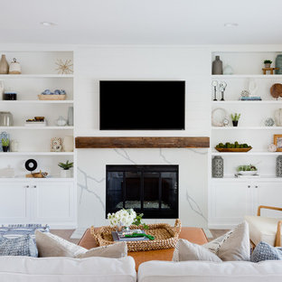 This is an example of a coastal enclosed family and games room in Orange County with white walls, medium hardwood flooring, a standard fireplace, a wall mounted tv and brown floors.
