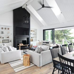 Inspiration pour une salle de séjour rustique ouverte avec un mur blanc, un sol en bois clair, une cheminée standard et un téléviseur fixé au mur.