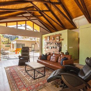 Cette photo montre une salle de séjour rétro ouverte avec un mur vert et un sol en bois brun.