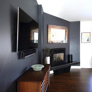 カルガリーの中サイズのミッドセンチュリースタイルのおしゃれなファミリールーム (グレーの壁、無垢フローリング、標準型暖炉、漆喰の暖炉まわり、壁掛け型テレビ) の写真