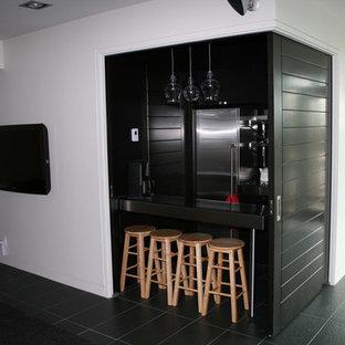 Ejemplo de sala de estar con barra de bar abierta, minimalista, pequeña, con paredes blancas, suelo de pizarra, televisor colgado en la pared y suelo negro