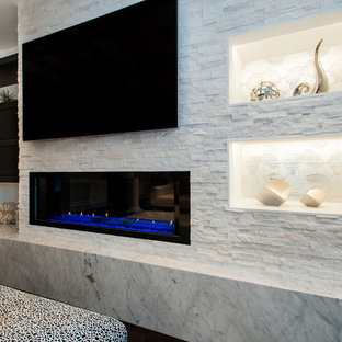 Photo of a large modern family room in Seattle with grey walls, medium hardwood floors, a standard fireplace, a stone fireplace surround and a built-in media wall.