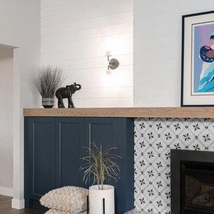Foto di un grande soggiorno minimalista aperto con pareti grigie, pavimento in vinile, camino classico, cornice del camino piastrellata, pavimento grigio, soffitto in perlinato e pareti in perlinato