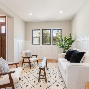 Esempio di un soggiorno country aperto e di medie dimensioni con pareti beige, nessun camino, nessuna TV, parquet chiaro, pavimento beige e boiserie