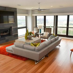 Стильный дизайн: большая двухуровневая гостиная комната в современном стиле с серыми стенами, полом из бамбука, стандартным камином, телевизором на стене, фасадом камина из камня и оранжевым полом - последний тренд