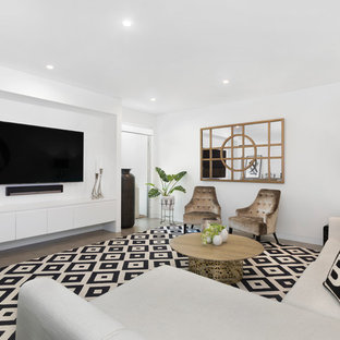 Photo of a contemporary family room in Sydney with white walls, a wall-mounted tv and grey floor.