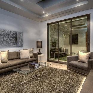 Foto de sala de estar minimalista, pequeña, sin chimenea, con paredes beige, suelo de piedra caliza y televisor colgado en la pared