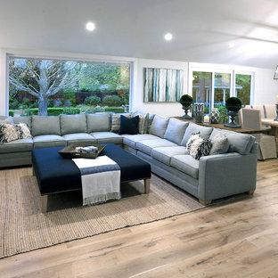 Esempio di un soggiorno country di medie dimensioni e aperto con angolo bar, pareti bianche, parquet chiaro, nessun camino, TV a parete e pavimento beige