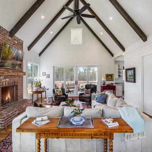 Exempel på ett stort lantligt allrum med öppen planlösning, med vita väggar, mellanmörkt trägolv, en spiselkrans i tegelsten, en väggmonterad TV, brunt golv och en standard öppen spis
