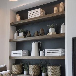 Imagen de sala de estar abierta, campestre, con paredes blancas, suelo de madera clara, chimenea tradicional, marco de chimenea de piedra y televisor colgado en la pared