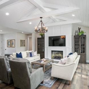 Diseño de sala de estar abierta, campestre, con paredes blancas, suelo de madera clara y pared multimedia