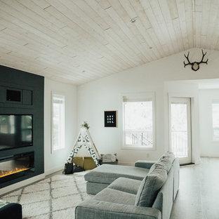 バンクーバーの中サイズの北欧スタイルのおしゃれなファミリールーム (白い壁、壁掛け型テレビ、横長型暖炉、クッションフロア) の写真