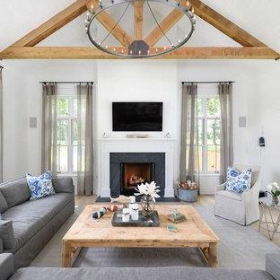 Modelo de sala de estar de estilo de casa de campo con paredes blancas, suelo de madera clara, chimenea tradicional y televisor colgado en la pared