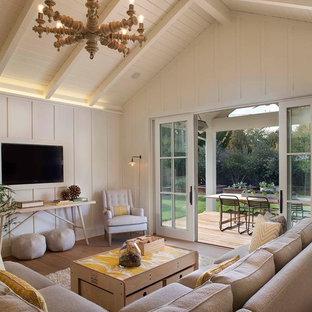 Modelo de sala de estar de estilo de casa de campo, sin chimenea, con paredes blancas, televisor colgado en la pared y suelo de madera en tonos medios