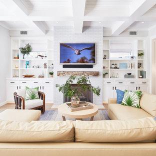 ロサンゼルスのビーチスタイルのおしゃれなファミリールーム (白い壁、無垢フローリング、標準型暖炉、レンガの暖炉まわり、壁掛け型テレビ、茶色い床) の写真