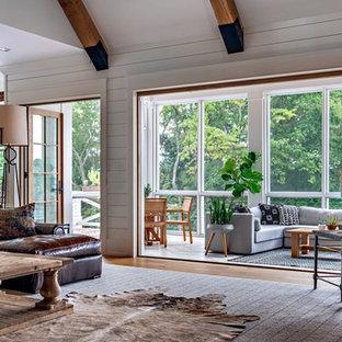 Ejemplo de sala de estar abierta, campestre, de tamaño medio, con paredes blancas, suelo de madera en tonos medios, chimenea tradicional, marco de chimenea de ladrillo, televisor colgado en la pared y suelo marrón