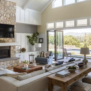 Modelo de sala de estar abierta, campestre, grande, con paredes amarillas, suelo de madera clara, chimenea tradicional, marco de chimenea de piedra, televisor colgado en la pared y suelo beige