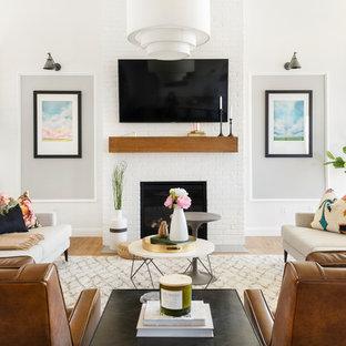 На фото: открытая гостиная комната в стиле современная классика с белыми стенами, светлым паркетным полом, стандартным камином, фасадом камина из кирпича, телевизором на стене и бежевым полом