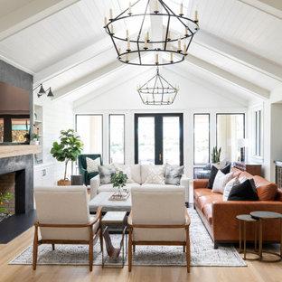 Aménagement d'une grand salle de séjour campagne ouverte avec un bar de salon, un mur blanc, un sol en bois clair, une cheminée standard et un téléviseur fixé au mur.