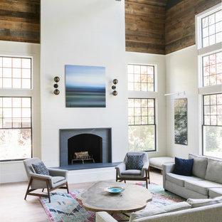 Ejemplo de sala de estar abierta, campestre, con paredes blancas, suelo de madera clara, chimenea tradicional y suelo beige